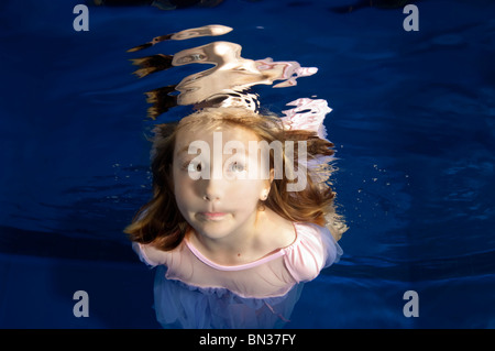 little girl making funny face underwater swimming - Stock Photo