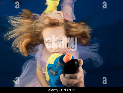 underwater portrait of little girl (8 years old) holding water gun in swimming pool - Stock Photo