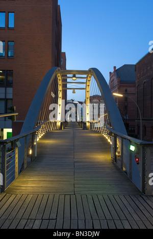 Illuminated footbridge in the old warehouse district (Speicherstadt), Hamburg, Germany - Stock Photo