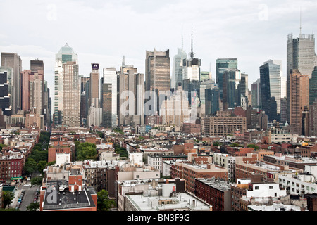 view looking east at sundown across low roofs of old housing stock in Hells Kitchen to mid Manhattan skyline towers - Stock Photo