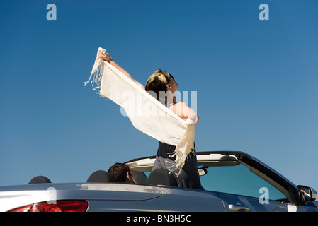 Woman standing up in convertible with arms outstretched - Stock Photo