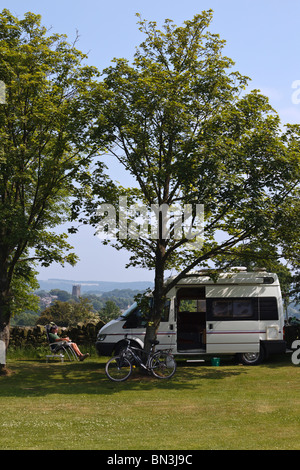 Cyclist relaxing next to his campervan at a campsite in the Derbyshire Peak District. - Stock Photo