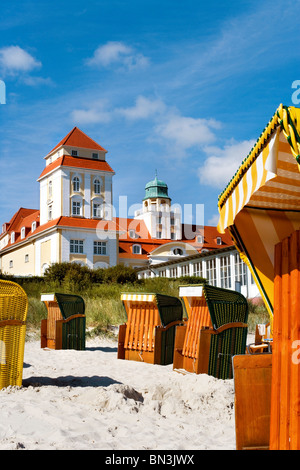 Hooded Beach Chairs on the beach of Binz, spa hotel in the background, Ruegen, Germany - Stock Photo