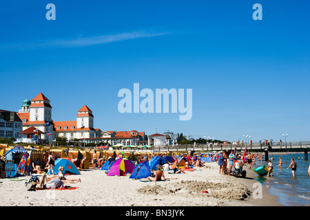 Tourists on the beach of Binz, spa hotel in the background, Ruegen, Germany - Stock Photo