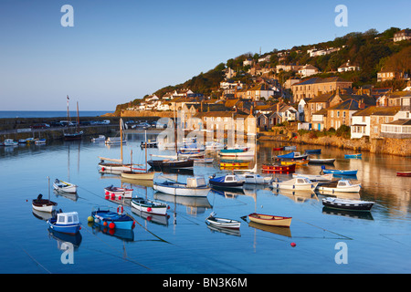 The first light of dawn catching the cottages along the waterfront, overlooking the picturesque Cornish Harbour - Stock Photo