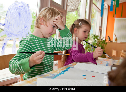 Young boy and girl painting in the kindergarten - Stock Photo