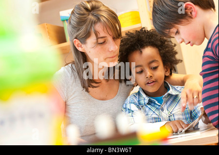 Kindergarten teacher and children looking at book, low angle view - Stock Photo