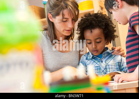 Kindergarten teacher reading children, low angle view - Stock Photo