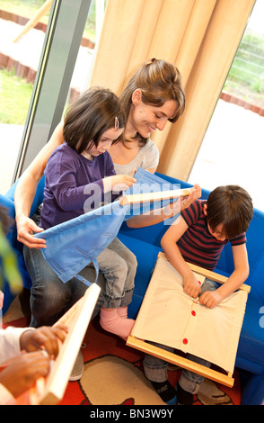 Children playing with fasteners frames - Stock Photo