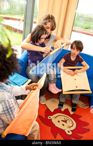 Kindergarten teacher and children playing fasteners frames, elevated view - Stock Photo