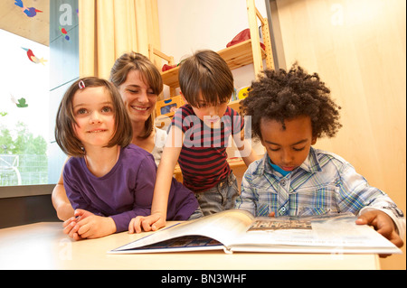 Kindergarten teacher and children looking at a book, low angle view - Stock Photo