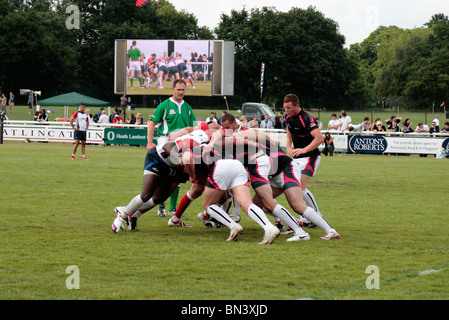 A scrum forms in a rugby seven's game, Richmond Rugby Club, Surrey, UK. June 2010 (some blur) - Stock Photo