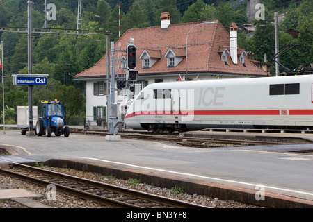 Swiss Alps region: Superfast ICE train and old tractor in Interlaken. - Stock Photo