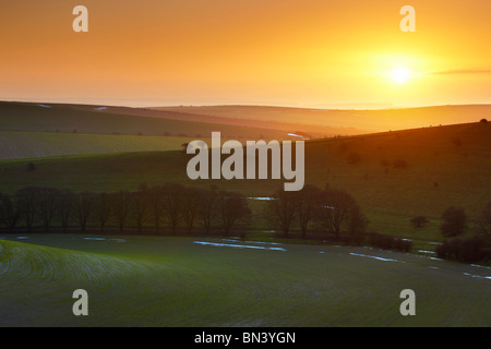 South Downs sunrise near Standean Bottom. Lying snow still visible around the edge of the fields. - Stock Photo