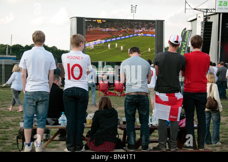 England fans watching the England V USA match from the South Africa World Cup on a large outdoor screen in June - Stock Photo