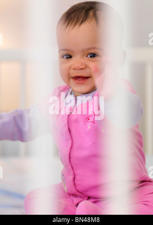 Cute seven month old smiling baby girl sitting inside a crib - Stock Photo