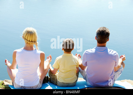 Rear view of three family members in pose of lotus on summer day - Stock Photo