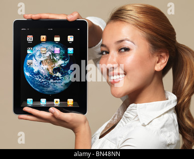 Smiling young woman with Apple iPad 3G tablet computer in her hands - Stock Photo