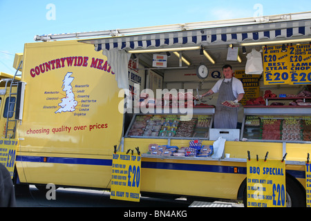 Butcher selling produce from his mobile stall at Dorchester Market - Stock Photo