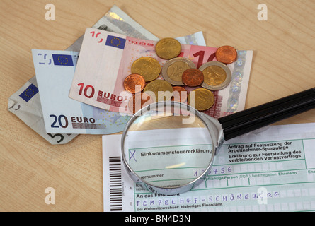 Income tax return under a magnifying glass. - Stock Photo
