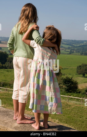 Two girls standing and looking out at countryside with arms around each other - Stock Photo