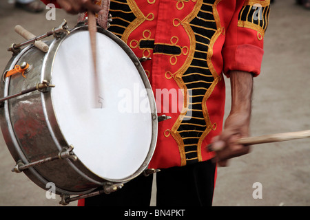 Musical instrument drum ; Artist playing drum in a band during religious procession - Stock Photo