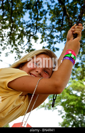 Pretty blond freckle faced Louisiana girl swinging from chain at Welch's Airboat Tours and Alligator Farm - Stock Photo