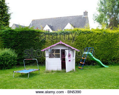 Pink Wendy House for children to play in in a garden - Stock Photo