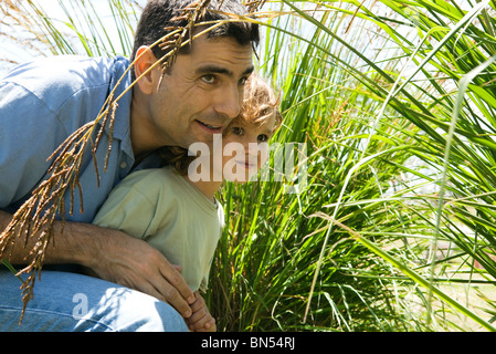 Father and son hiding in tall grass - Stock Photo