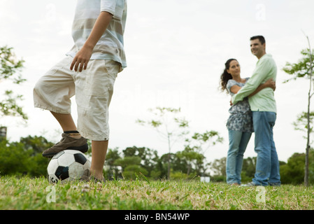Boy playing with soccer ball, parents watching and embracing in background - Stock Photo