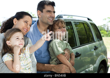 Family leaning against car, all looking as daughter points at something in distance - Stock Photo