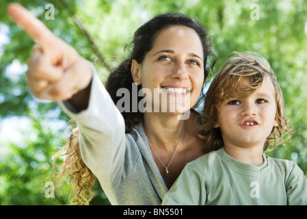 Mother pointing out something to young son outdoors - Stock Photo