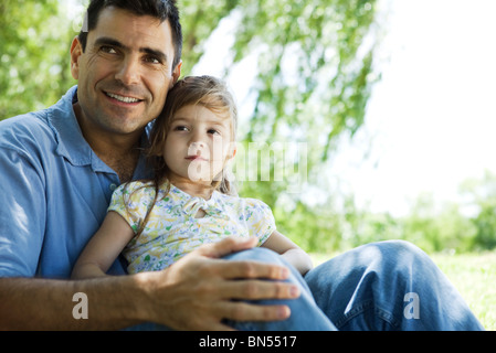 Father holding young daughter on lap outdoors - Stock Photo
