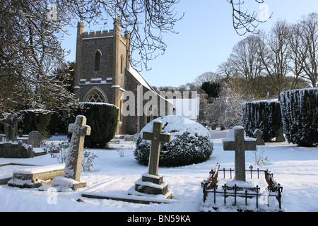 Remenham Church of Saint Nicholas and graveyard in snow, Berkshire, England, UK, blue sky - Stock Photo