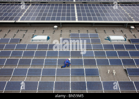 Construction of a big solar power plant, on a huge flat roof of a warehouse. - Stock Photo