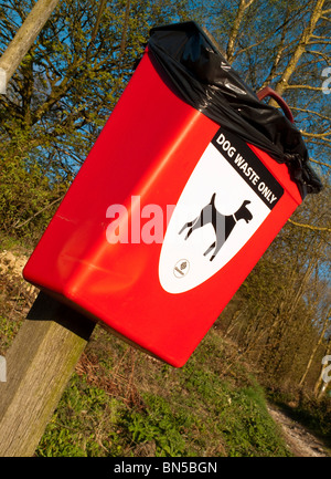 Red Dog Waste bin on a public footpath in the UK countryside - Stock Photo