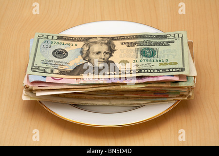 pile of money on plate US $20 Dollar Bill on Top - Stock Photo