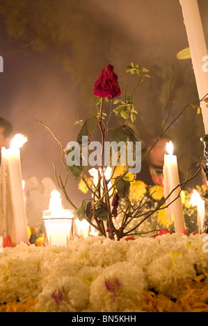Flowers and candles over a tomb in Mixquic cemetery  during la Alumbrada on the day of the dead - Stock Photo