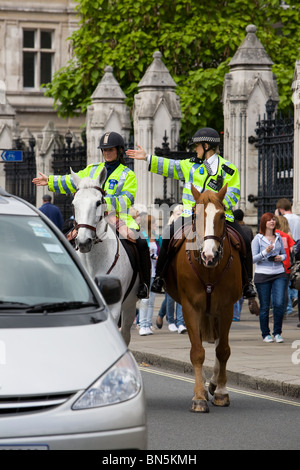 Two female mounted police officers, one of them a support officer, on patrol outside the Houses of Parliament - Stock Photo