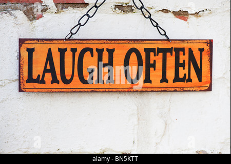 Laugh often. Old metal garden signs on a painted brick wall - Stock Photo