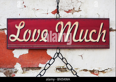 Love much. Old metal garden sign on a painted brick wall - Stock Photo