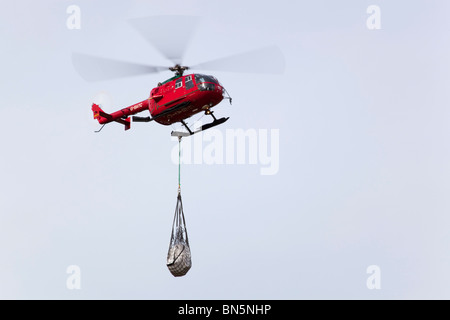 Helicopter carrying a load; Cornwall - Stock Photo
