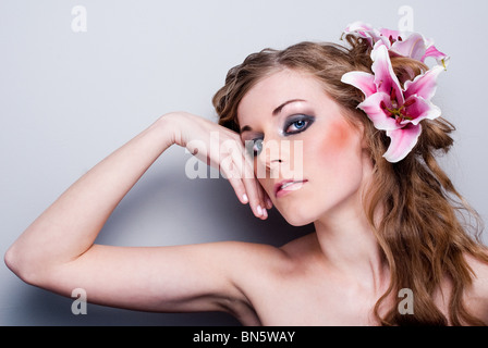 Beautiful young woman with lily flower. Isolated on white background - Stock Photo