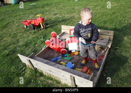 Toddler boy in the garden playing in a sandpit with plastic toys MODEL RELEASED - Stock Photo