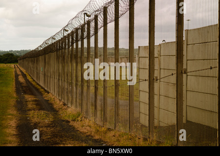 Outer fence of a high security prison topped with razor wire - Stock Photo
