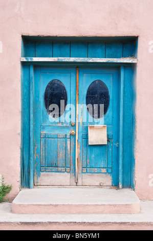 Painted in traditional blue to keep evil at bay, this old door set into an adobe wall is found in Tularosa, New - Stock Photo