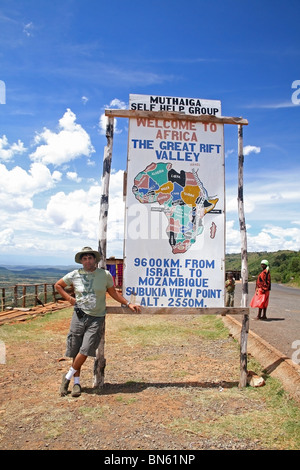 A tourist posing near the signboard of 'The Great Rift Valley' on a highway leading to Lake Nakuru in Kenya, East - Stock Photo