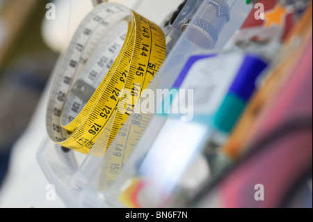 A curled up tape measure on needlework bench. - Stock Photo