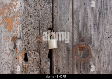 Old wooden planks door locked with rusty nails - Stock Photo