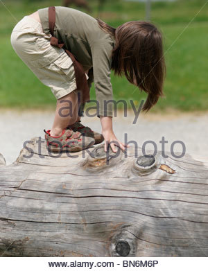 Toddler climbing on a tree trunk bending over sideways touching the wood play outdoors - Stock Photo